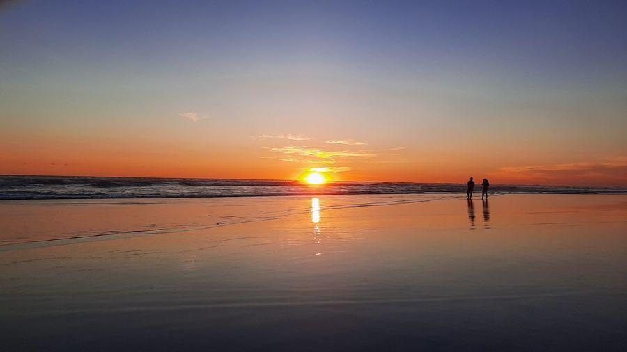 Lover couple walking on wet sand beach at sunset