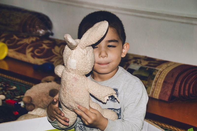 Close-up of cute boy holding toy at home