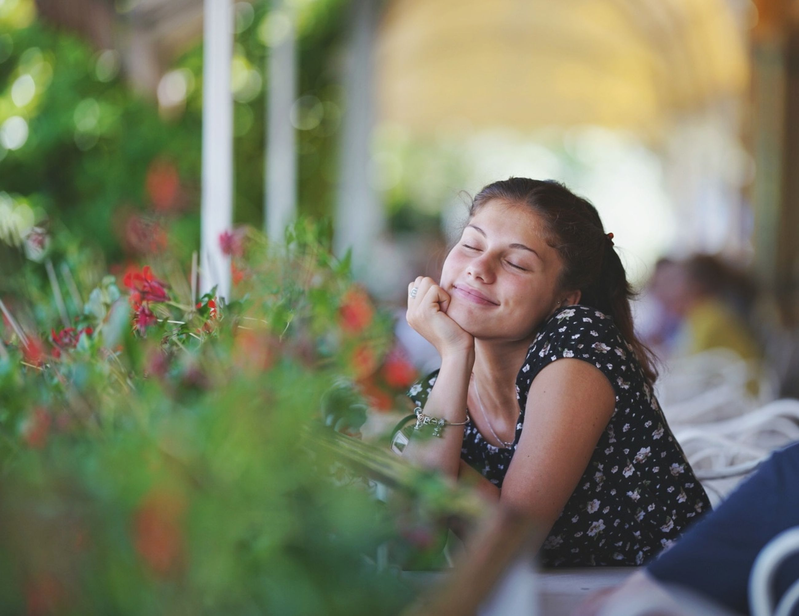 child, one person, childhood, girls, selective focus, real people, leisure activity, smiling, lifestyles, women, casual clothing, happiness, portrait, plant, females, flower, sitting, day, innocence, outdoors, hairstyle