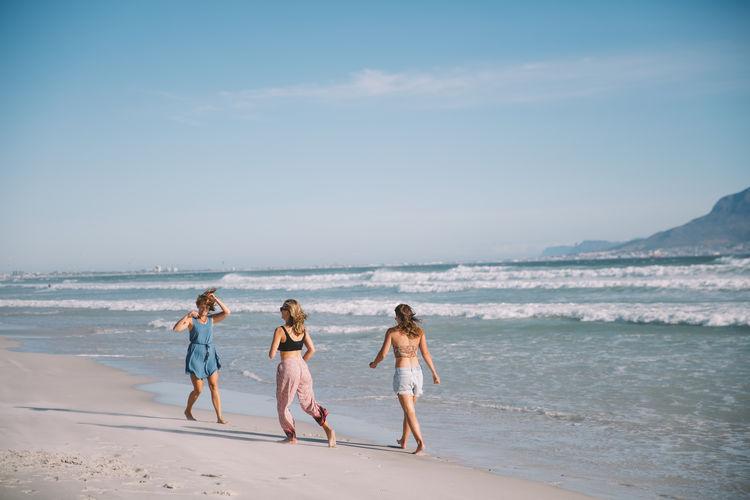 Female friends enjoying at beach against sky