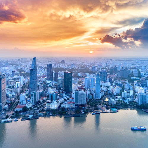 Aerial view of city by river against cloudy sky during sunset