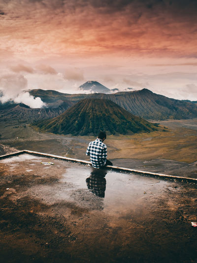 Reflection Of Man In Puddle Against Mountain Range