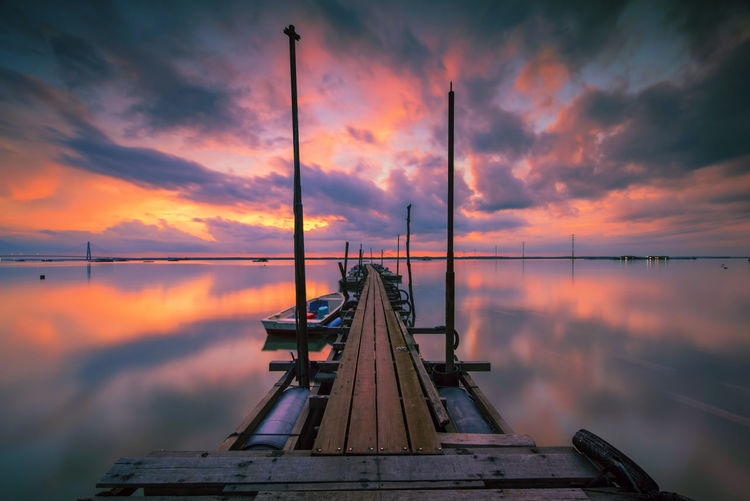Low angle view of jetty in sea against sunset sky