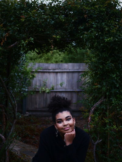 Portrait Of Smiling Young Woman Sitting Against Trees In Backyard