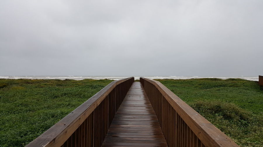 Footbridge over land against sky