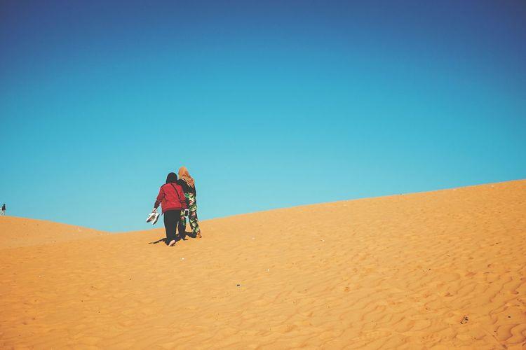 Person walking on sand dune in desert against clear sky
