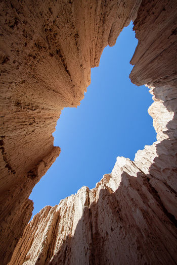 Low angle view of rock formation against clear blue sky. slot canyon
