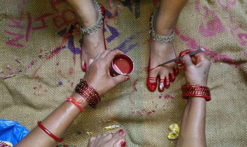 High Angle View Of Woman Applying Henna On Foot