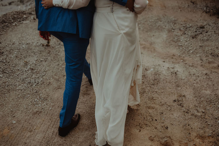 Low section of couple walking on dirt road