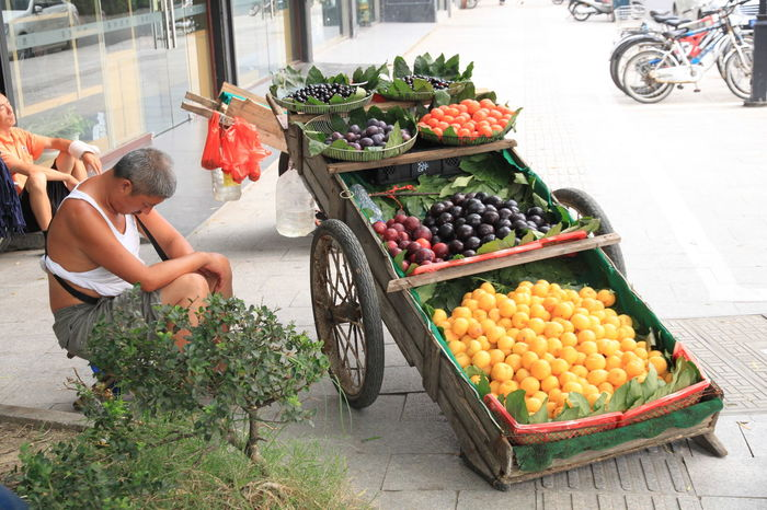 Merchant Sidewalk Street Life Street Vendor Colorful Exhausted Fruit Fruit Cart Fruits One Person Outdoors Real People Resting Retail  Street Food Street Photography Street Side Streetphotography Tired Vendor