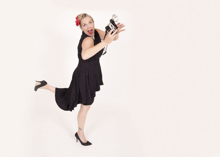 Side view of mature woman in black dress holding camera while standing against white background