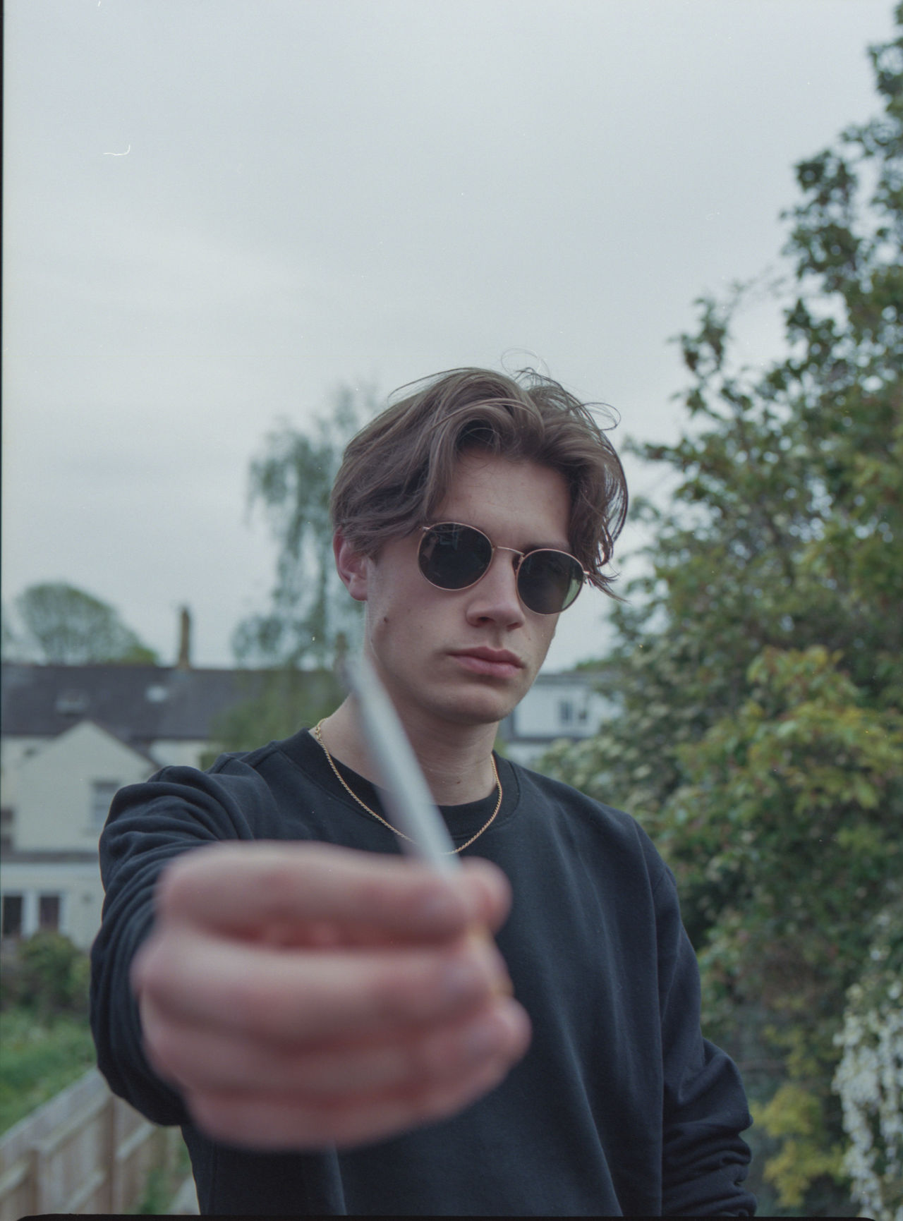 PORTRAIT OF YOUNG MAN WEARING SUNGLASSES STANDING AGAINST WALL