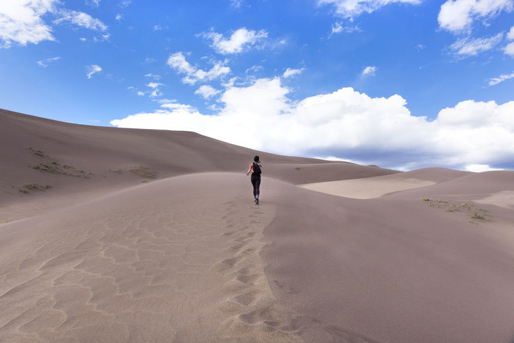 Rear View Of Woman Running On Sand Dune In Desert Against Sky