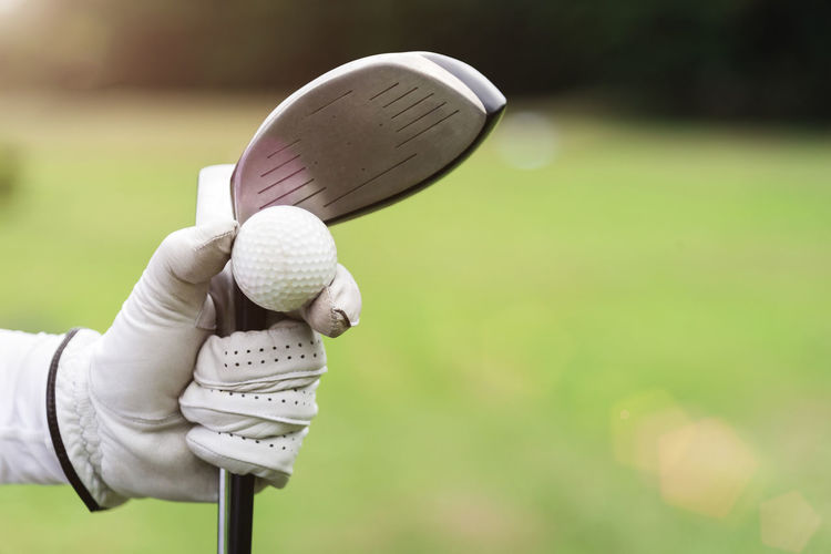 Cropped hand holding golf ball and club