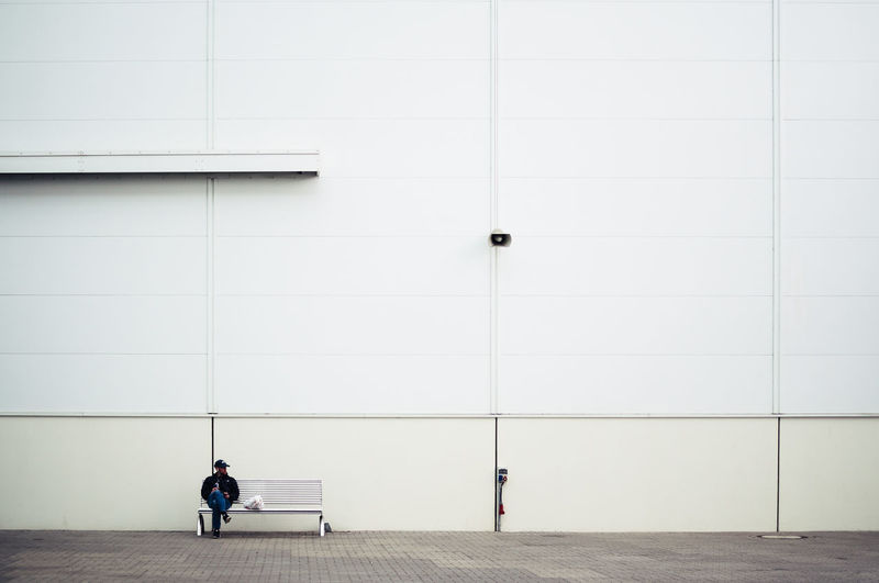 Man Sitting On Bench Against White Wall