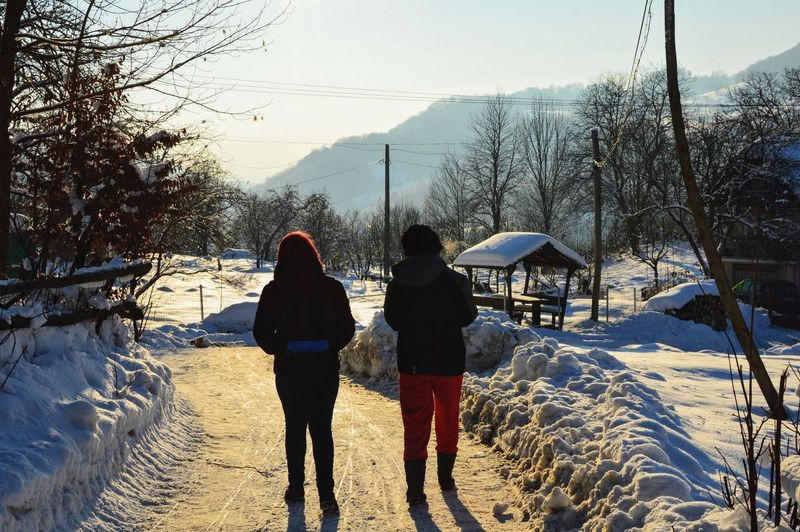 Rear view of women walking on snow covered landscape against sky