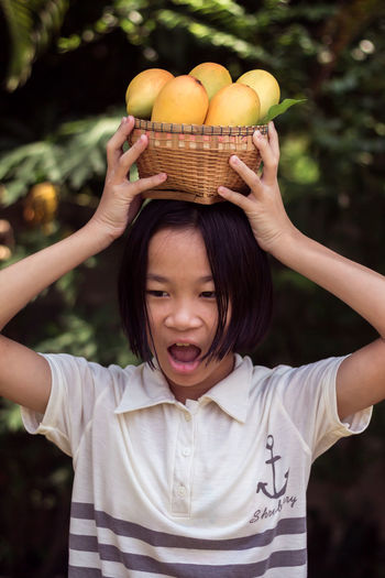 Girl carrying mango fruits with basket on head at farm