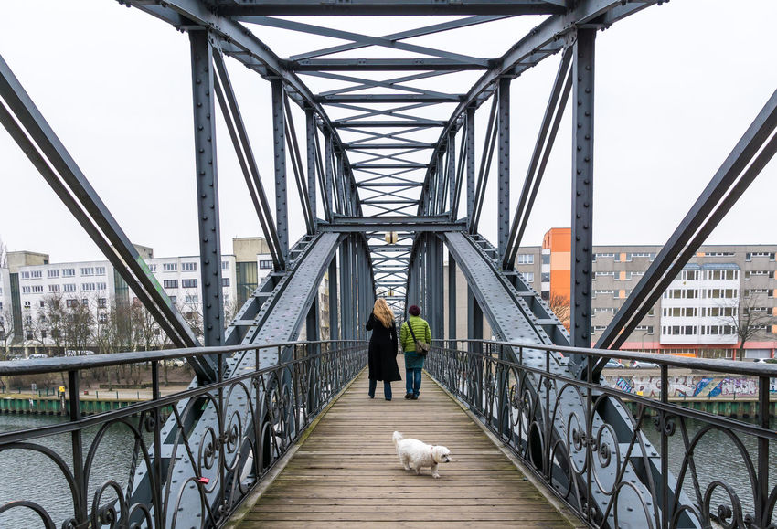 Adult Adults Only Bridge - Man Made Structure City Connection Day Dog Full Length Headwear Industry Maltese Malteser Men Outdoors People Pet Sky Suspension Bridge Two People Two Persons Walking Walking Around Working Young Adult