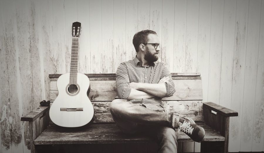Man sitting by guitar on bench against wall