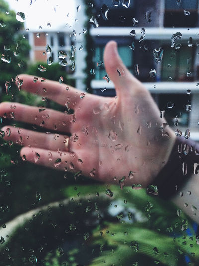 Cropped Image Of Hand Seen Through Wet Glass Window During Rainy Season