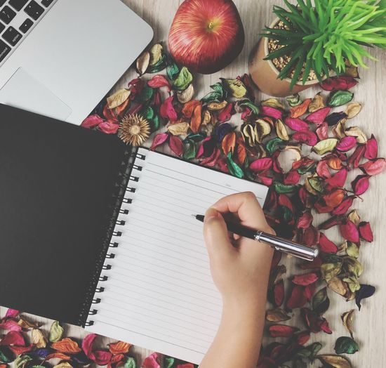 High angle view of person hand writing in diary by laptop on table