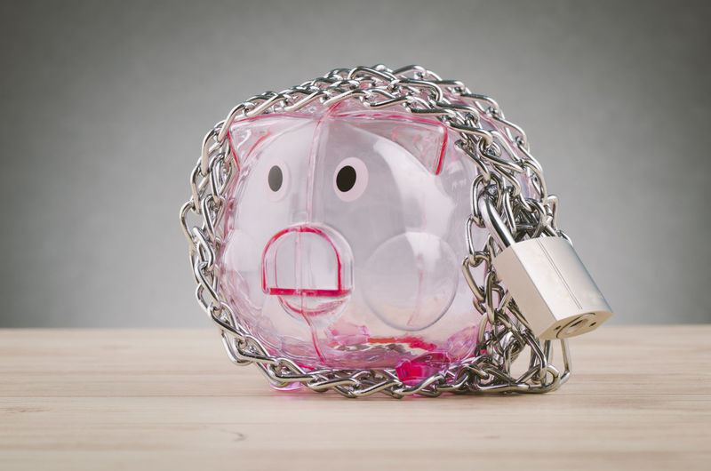 piggy bank surrounded by chains and padlock on wooden desk Table Still Life Indoors  Pink Color Close-up Savings No People Jar Piggy Bank Investment Container Glass - Material Art And Craft Wood - Material Representation Finance Transparent Currency Studio Shot Creativity