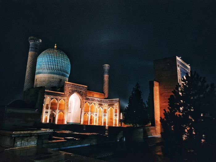 Low angle view of illuminated mosque in city at night