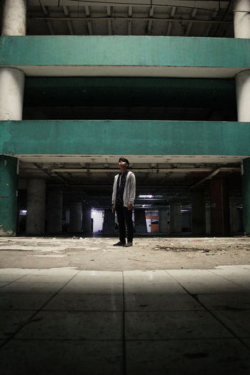 Full length portrait of young man standing against built structure