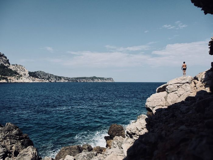 Rear view of shirtless man standing on rock formations by sea against sky