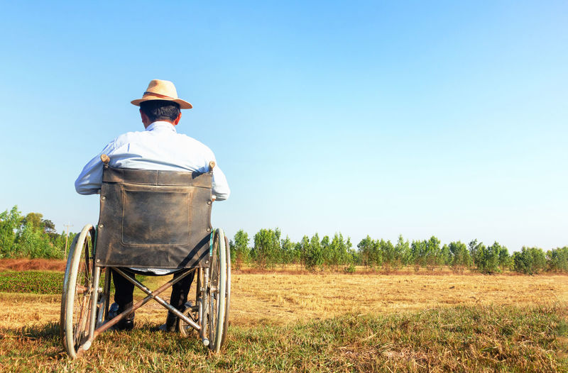 Rear view of man sitting on wheelchair against sky