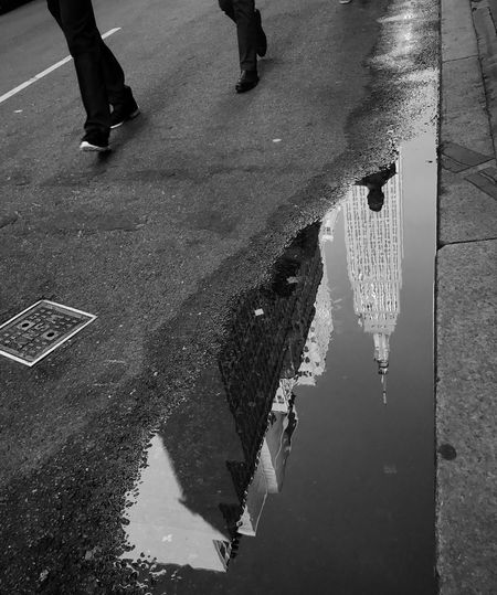 Low section of people walking on wet street