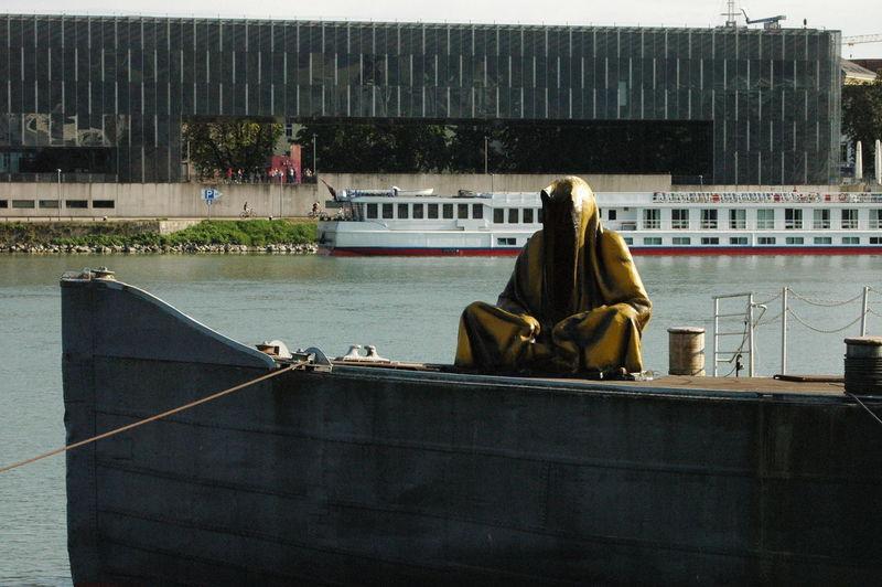 Rear view of men sitting on riverbank
