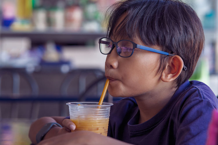 Close-up of boy drinking juice at restaurant