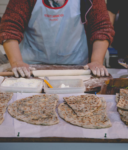Older woman kneading a flat naan bread at stall on the traditional food market in London Adult Baking Flat Bread Flour Food Food Market Freshness Grain Handmade Lifestyles Market Stall Naan Occupation One Woman Only Preparing Food Retail  Sale Save Food Share Food Superfood Trade Traditional Vegetarian Whole Meal Women