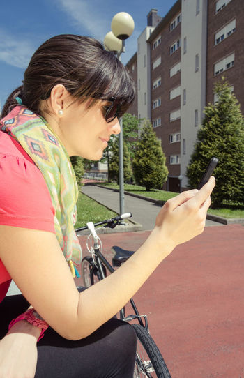 Woman using mobile phone while sitting on bench by bicycle