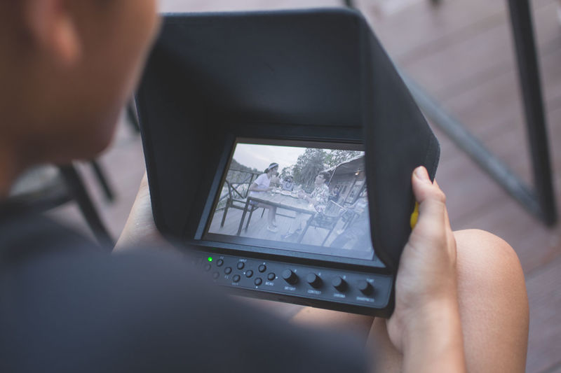 Midsection of man using digital tablet while sitting outdoors