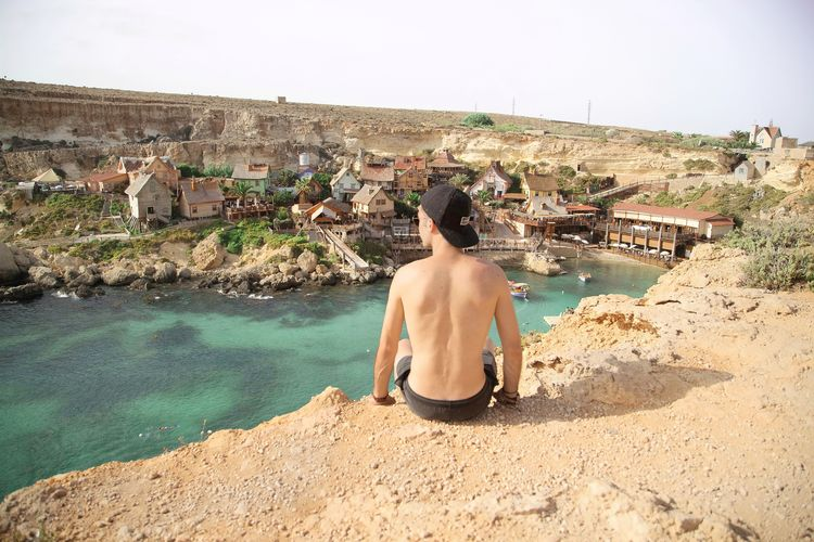 Rear view of shirtless man sitting against sky