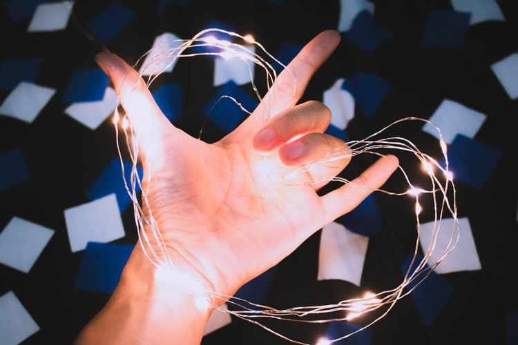 Cropped hand of person holding illuminated lighting equipment in heart shape at home