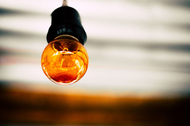 Close-up of light bulb hanging in room