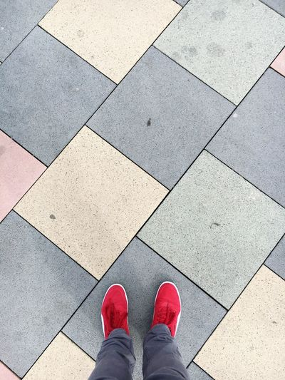 Low Section Of Person Wearing Red Shoes On Footpath