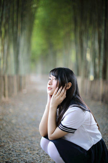 Side view of young woman crouching in bamboo groove