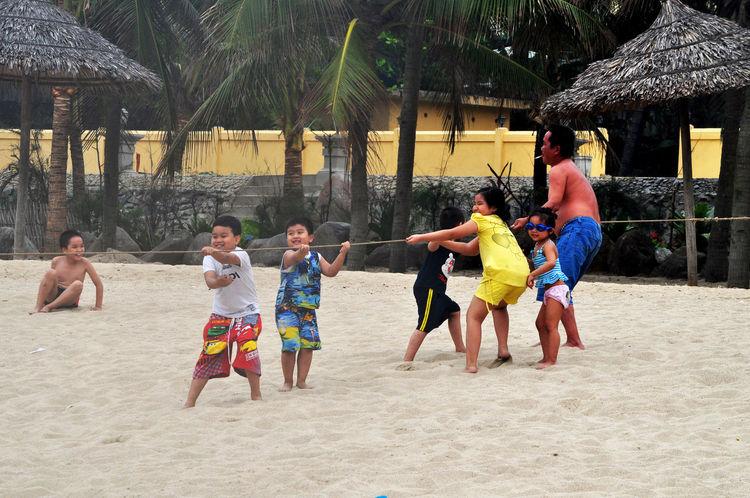 Children help pull in fishing net on beach in Da Nang, Vietnam. Beaches Children Cigarettes Fathers Fishing Fishing Nets Fun Hauling Pulling Ropes Smoking Thatch White Sand
