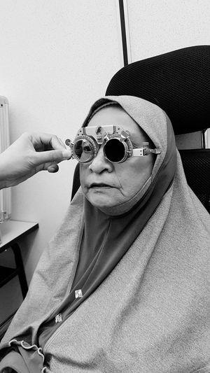 Cropped hand of optician testing woman eyesight