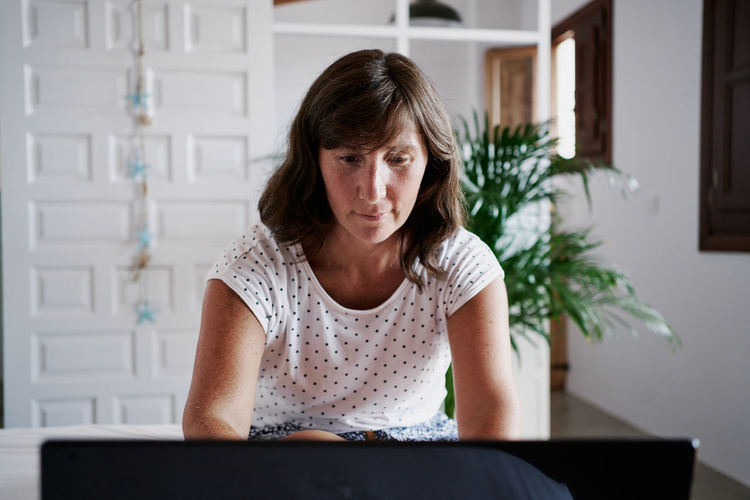 Portrait of woman sitting on table at home