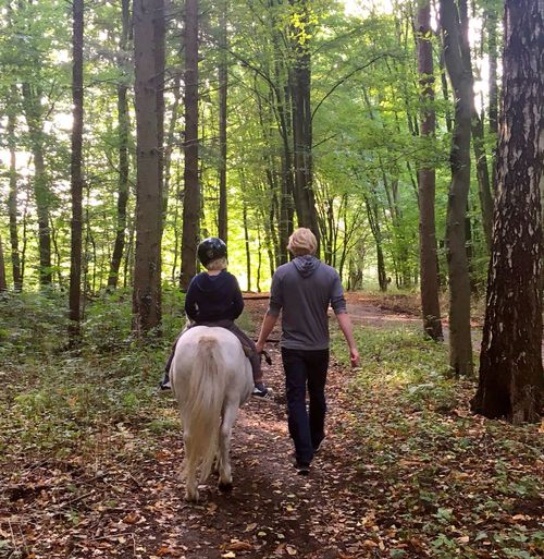 Pony riding Forest Rear View Two People Togetherness Nature Trees Nature WoodLand Pets Dog Tree Footpath Adults Only Walking Adult Men People Bonding Travel Destinations Friendship Tree Trunk