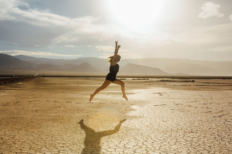 Side view of young woman jumping at desert against sky during sunny day