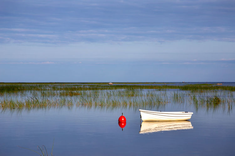 Red boat floating on lake against sky