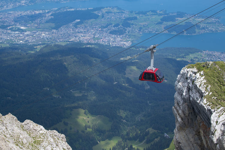 A gondola lift or aerial tramway lifting tourists to the top of a mountain. switzerland