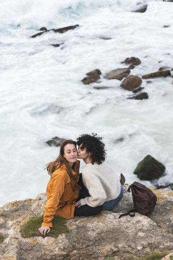 Young couple on rock at sea shore