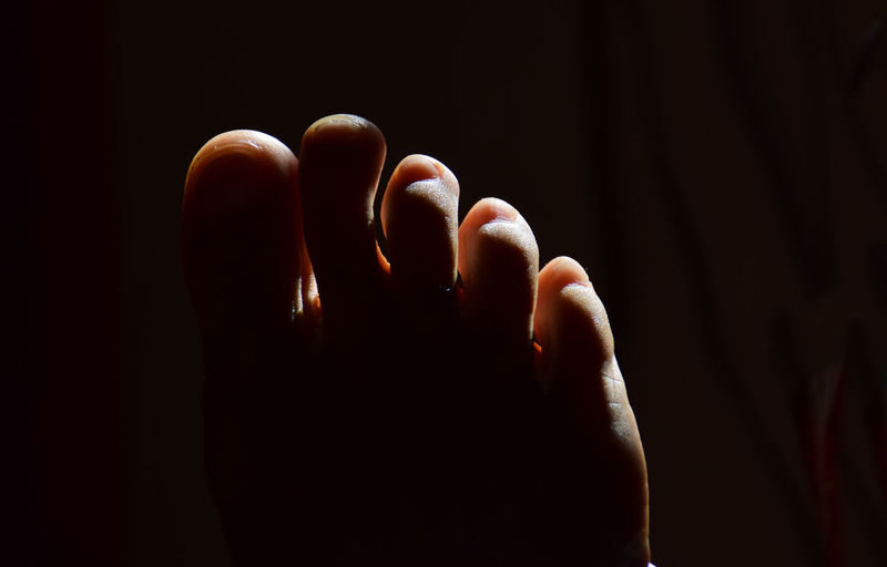 Close-up of human foot against black background